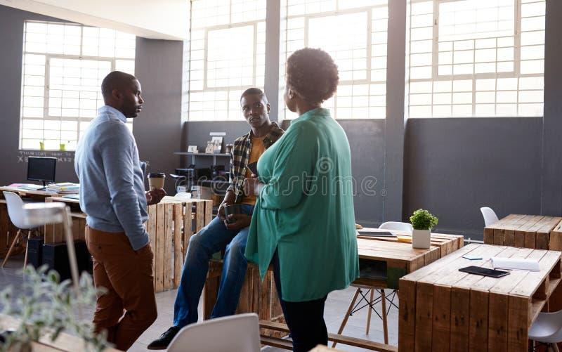 Trzy Afrykańskiego praca kolegi opowiada wpólnie w moden biurze obrazy royalty free
