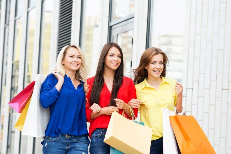 Trzy atrakcyjnego szczęśliwego żeńskiego przyjaciela chodzi w centrum miasta z torba na zakupy obraz stock