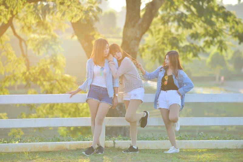 Trzy azjatykciego młodego ladys cieszą się popołudniowego upał w ogródzie zdjęcie stock