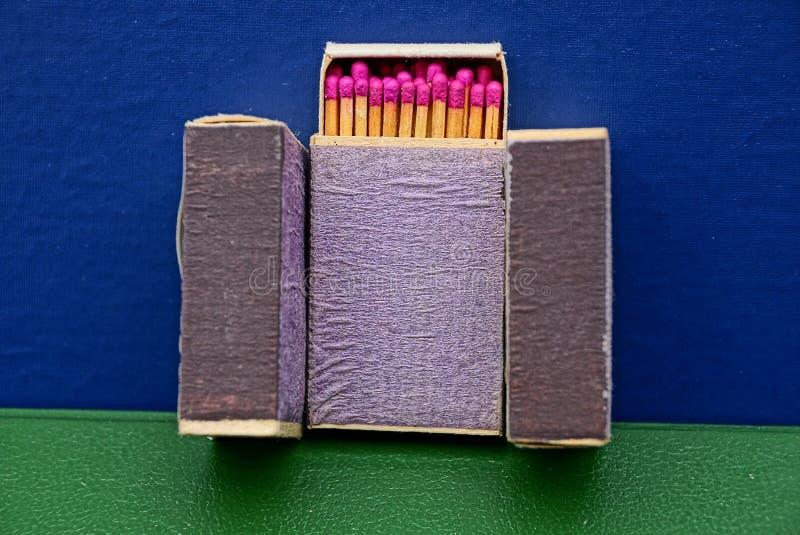 Trzy błękitnego pudełka z dopasowaniami na stole obrazy stock
