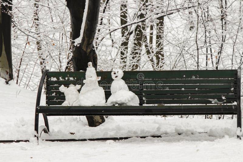 Trzy bałwanu na ławce w zima lesie fotografia royalty free