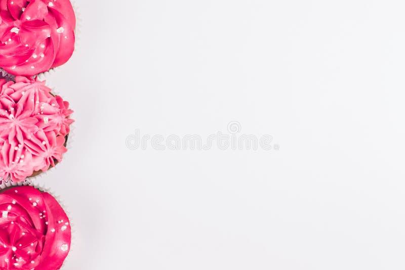 Trzy babeczki z czerwieni i menchii lodowaceniem obramia białego tło Odgórny widok obraz stock