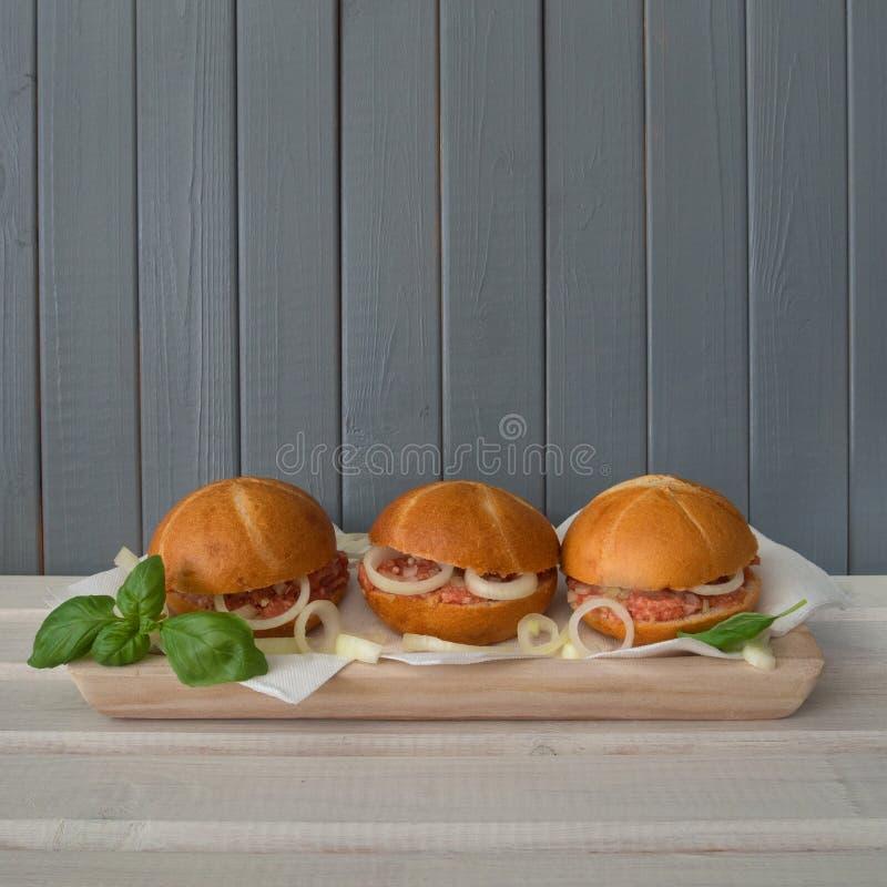 Trzy babeczki z surową minced wieprzowiną - mett, na szarobiałym drewnianym tle obraz stock