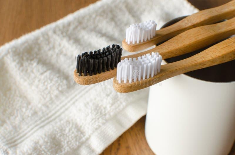 Trzy Bambusowego rodzinnego toothbrushes z białym ręcznikiem na drewnianym tle obrazy royalty free