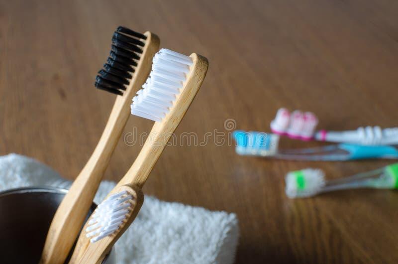 Trzy Bambusowego toothbrushes przeciw trzy plastikowym toothbrushes na drewnianym tle zdjęcie royalty free