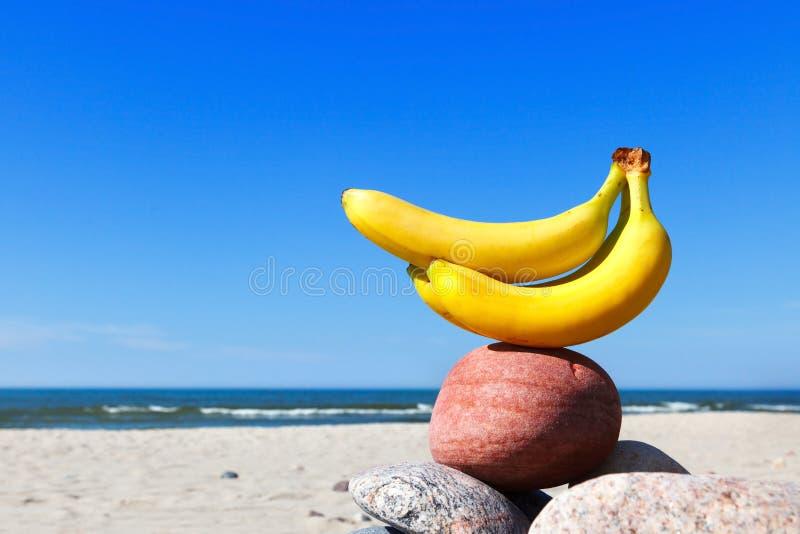 Trzy banana na plaży na tle niebieskie niebo i morze zdjęcia stock