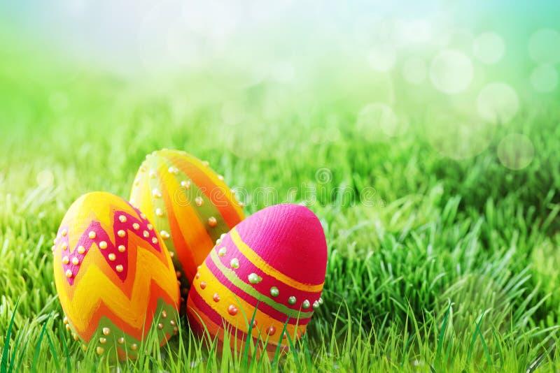 Trzy barwili Wielkanocnych jajka na trawie zdjęcie royalty free