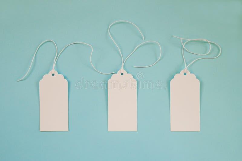 Trzy białej pustego papieru metki lub etykietki ustawiają na błękitnym tle zdjęcie stock