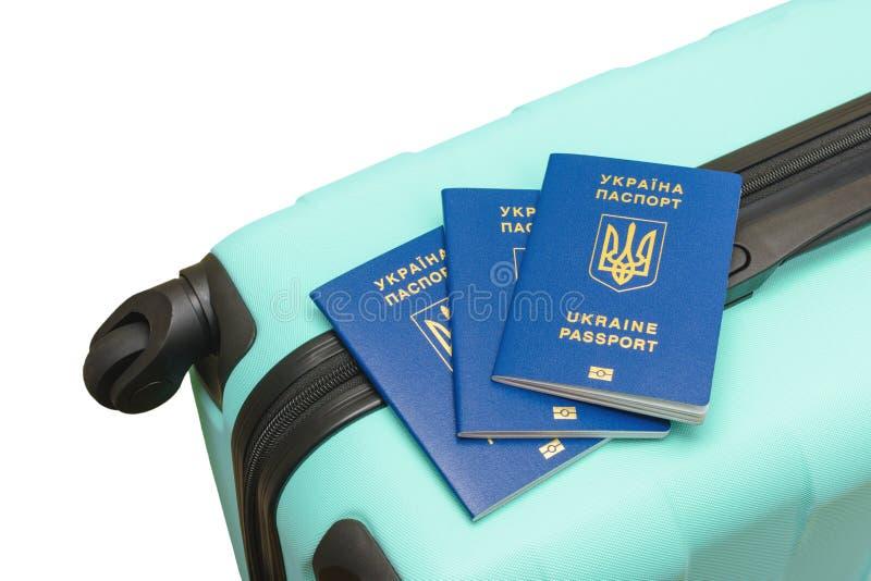 Trzy biometrycznego paszporta Ukraina na walizce odosobniony fotografia royalty free