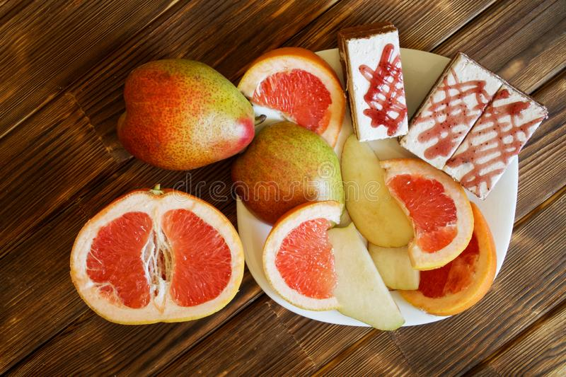 Trzy biskwitowego torta, plasterki grapefruitowy i bonkrety, k?amaj? w bia?ym talerzu na drewnianym stole robi? sosnowe deski Buf obraz royalty free