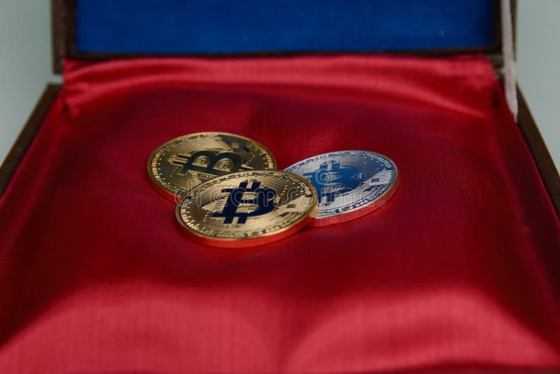 Trzy bitcoins kłamstwo na czerwonej szkatuły bazie obraz stock