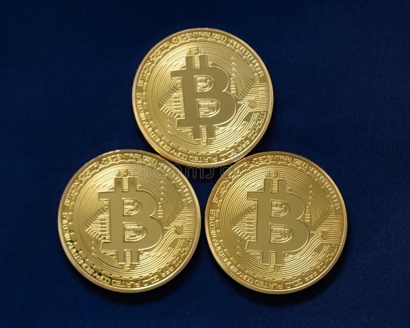 Trzy bitcoins odizolowywającego na błękicie fotografia stock