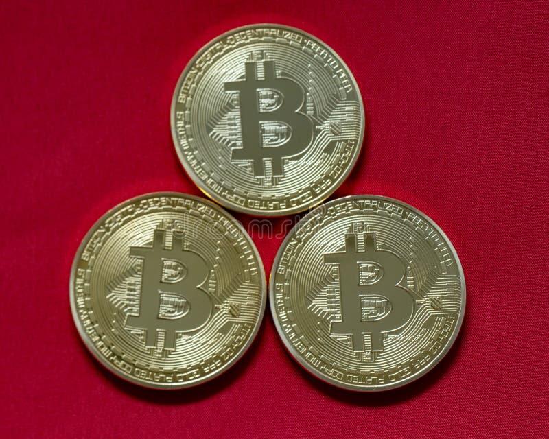 Trzy bitcoins odizolowywającego na czerwieni zdjęcie stock