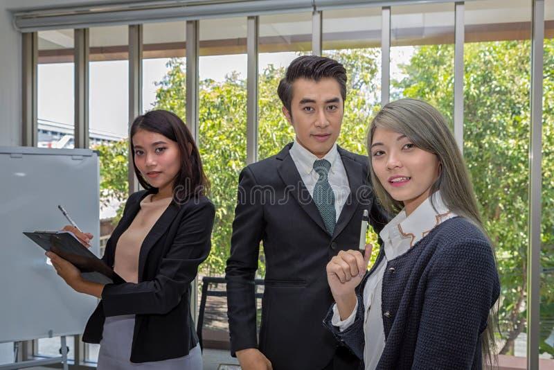 Trzy biznesmena w pokoju konferencyjnym Dru?yna pozuje w pokoju konferencyjnym przy biurem Azjatycki biznes Pracuj?cy brainstormi obraz royalty free