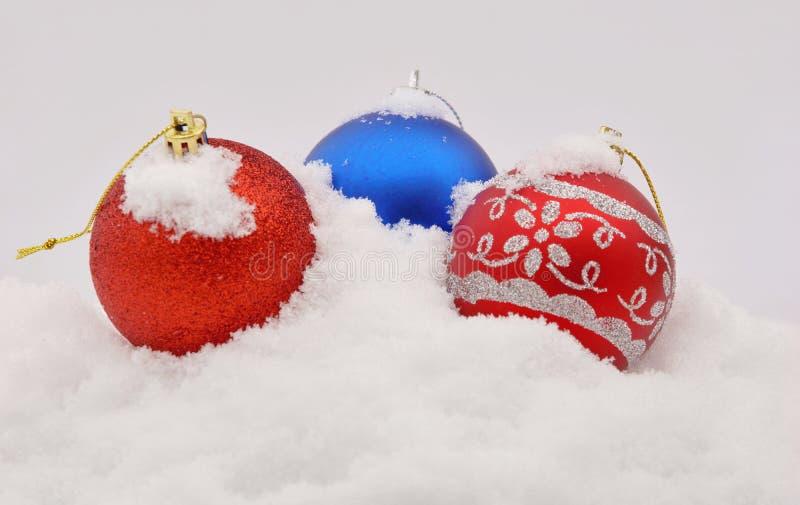 Trzy Bożenarodzeniowych piłek błękitna czerwień w śniegu fotografia royalty free