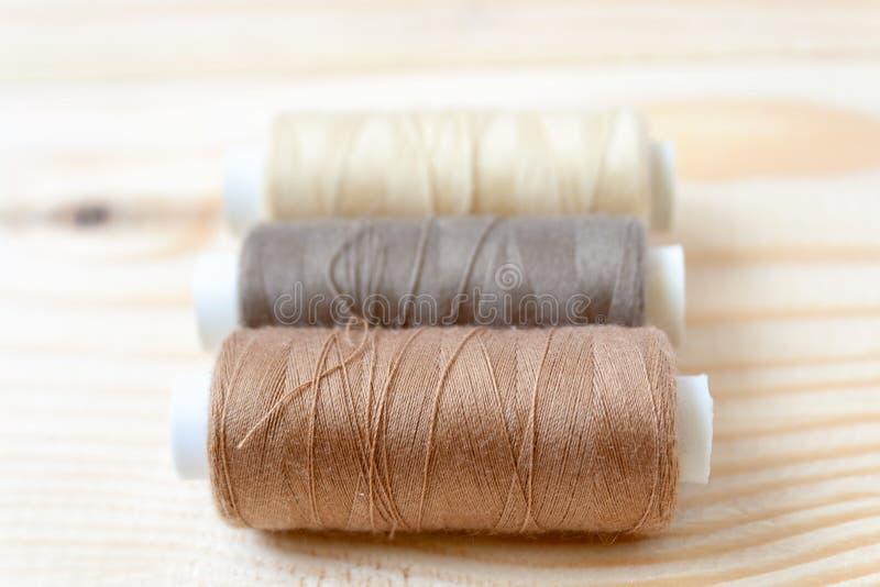 Trzy bobiny nici brązów cienie kłamają na drewnianym tle obraz stock