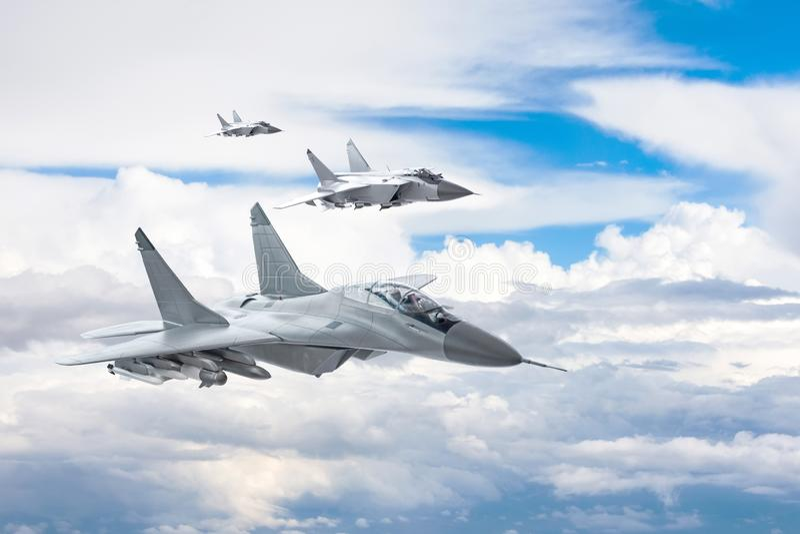 Trzy bojowy myśliwiec na misji wojskowej z broniami - rakiety, bomby, bronie na skrzydłach latają wysoko w niebie nad obraz royalty free