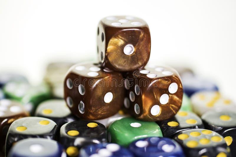 Trzy brąz miedzianej kostki do gry siedzi na barwionych kostkach do gry obraz stock