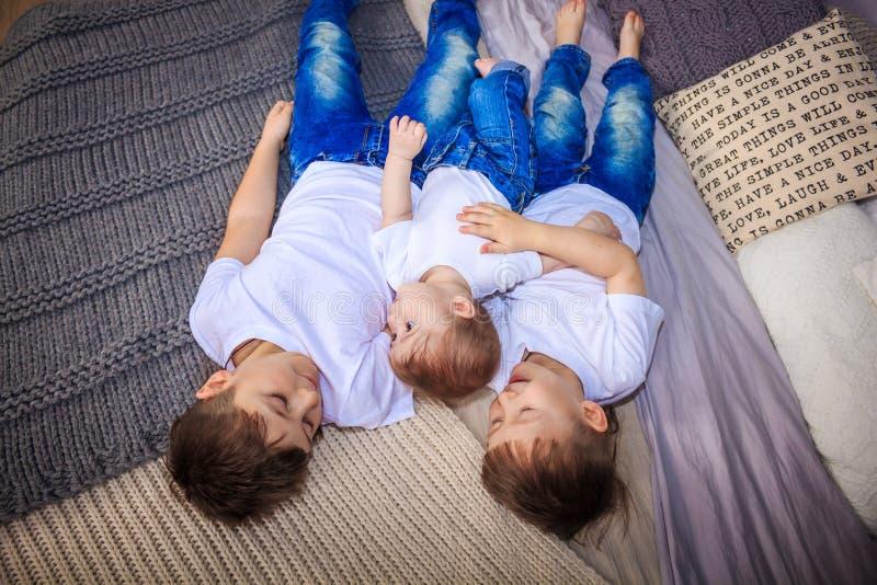 Trzy brata kłamają na łóżku braterskiej miłości duża rodzina, obrazy royalty free