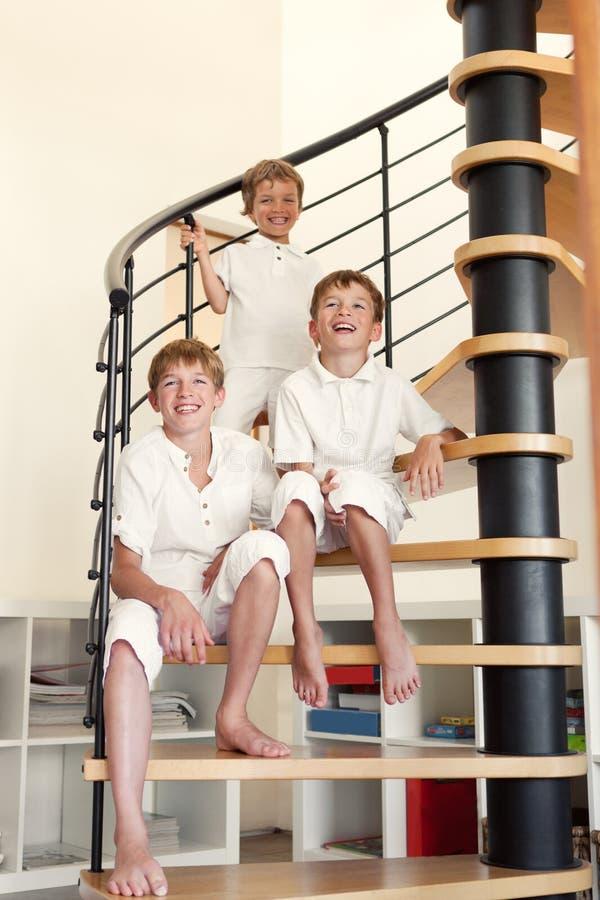 Trzy brata szczęśliwy obsiadanie na krokach. fotografia stock