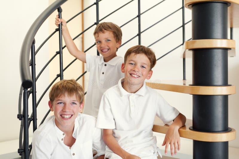 Trzy brata szczęśliwy obsiadanie na krokach. zdjęcie royalty free
