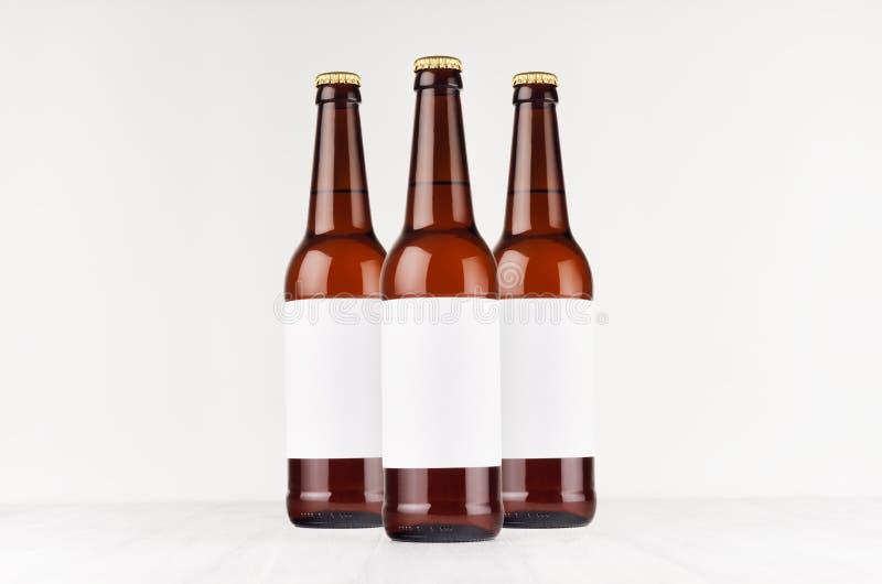 Trzy brown longneck piwnej butelki 500ml z pustą białą etykietką na białej drewnianej desce, wyśmiewają up fotografia stock