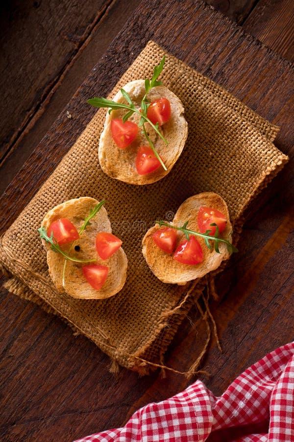Trzy Bruschette z pomidorem i Rakietową sałatką zdjęcie royalty free