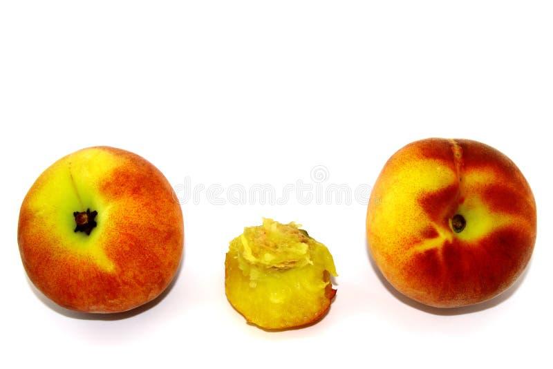 Trzy brzoskwini - dwa cały, jeden praktycznie jedzący kość na białym tle fotografia stock