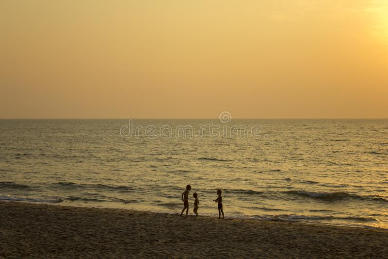 trzy ciemnej sylwetki dzieci na żółtym piasku plaża przeciw morzu i wieczór zdjęcie stock