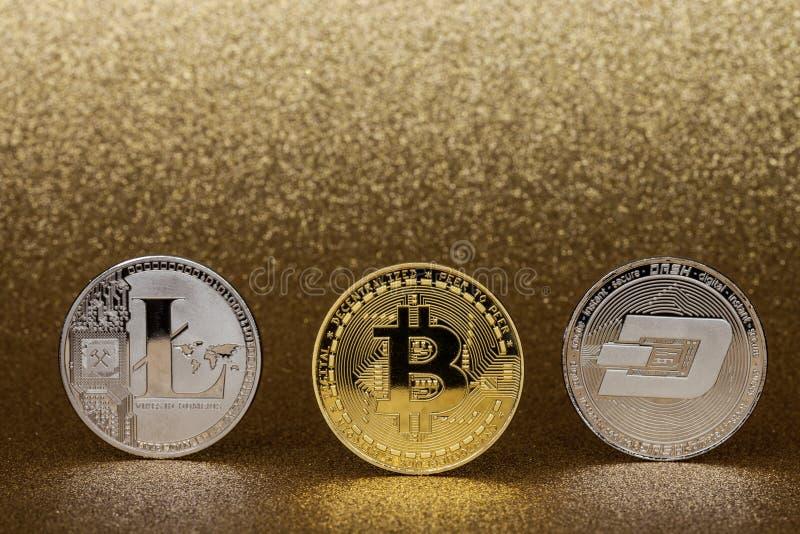 Trzy cryptocurrency monety złoty bitcoin, srebny litecoin i junakowanie moneta na glittery złotym tle, obraz stock