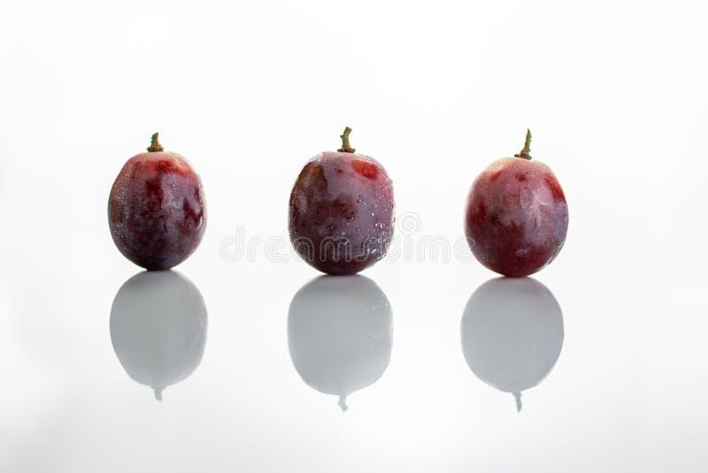 Trzy czerwieni mokrego winogrona odizolowywającego na białym tle obrazy stock