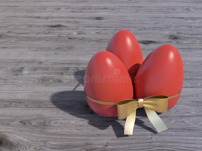 Trzy czerwonego Wielkanocnego jajka z złocistym łękiem zdjęcia stock