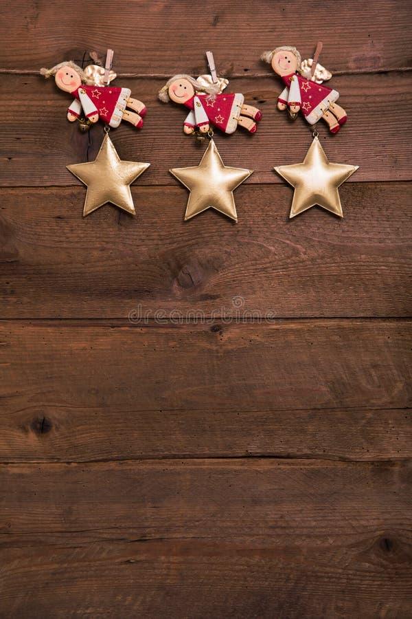 Trzy czerwony i złoci Bożenarodzeniowi aniołowie na starym drewnianym tle f obraz stock