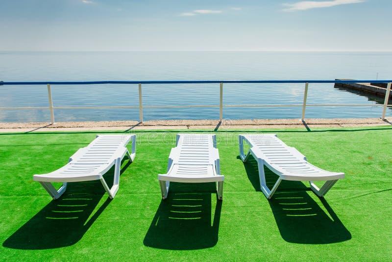 Trzy deckchairs na plaży, stawia czoło out morze obrazy stock