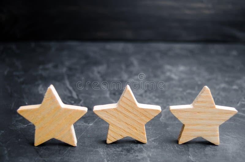 Trzy drewnianej gwiazdy na czarnym tle Pojęcie ocena cenienie krytycy, wizyta, i zdjęcie royalty free
