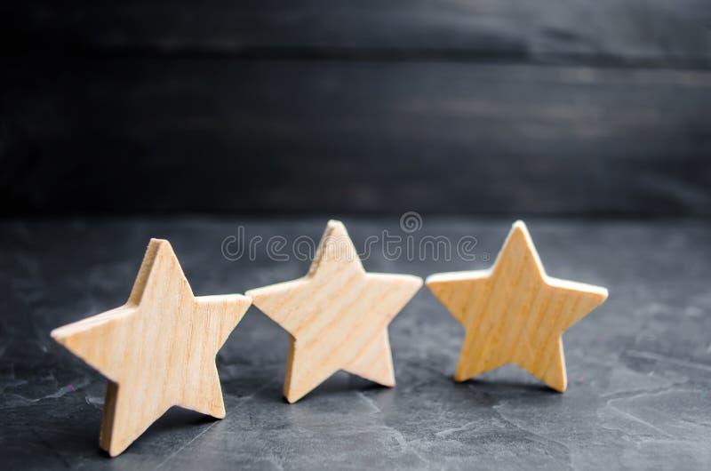 Trzy drewnianej gwiazdy na czarnym tle Pojęcie ocena cenienie krytycy, wizyta, i obrazy royalty free