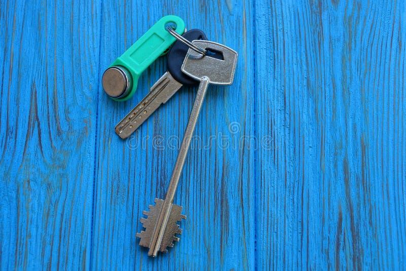 Trzy drzwiowego klucza w wiązce na błękitnym stole fotografia royalty free