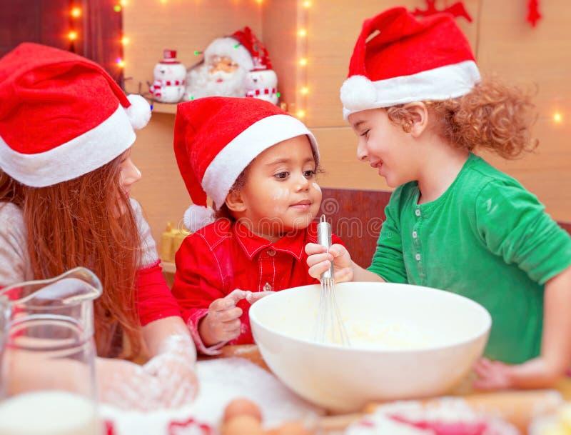 Trzy dzieciaka robi Bożenarodzeniowym ciastkom fotografia stock