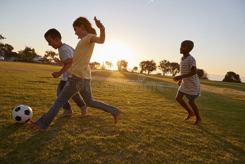 Trzy dziecka bawić się futbol w polu obraz stock