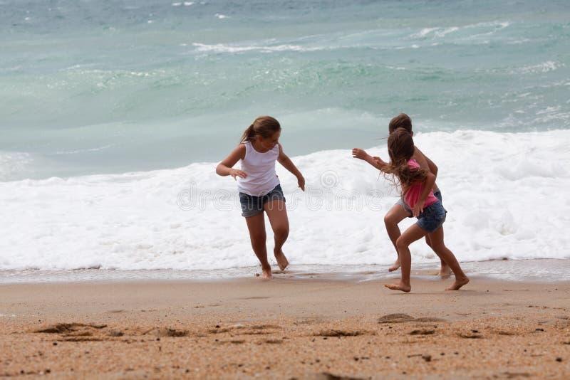 Trzy dziecka biega przy plażą fotografia royalty free
