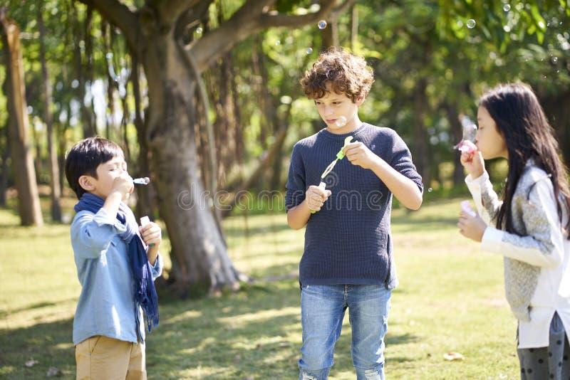 Trzy dziecka dmucha bąble w parku obrazy royalty free