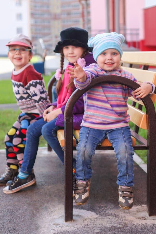 Trzy dziecka w jaskrawym odzieżowym obsiadaniu na ławce zdjęcie stock