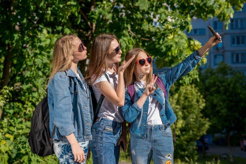 Trzy dziewczyna przyjaciół dziewczyny uczennica Lato w naturze W cajgach odziewa za plecakami Bierze obrazki ty dalej zdjęcia stock