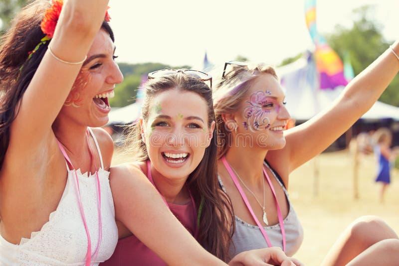 Trzy dziewczyna przyjaciela przy festiwalem muzyki, jeden obracali kamera zdjęcia royalty free