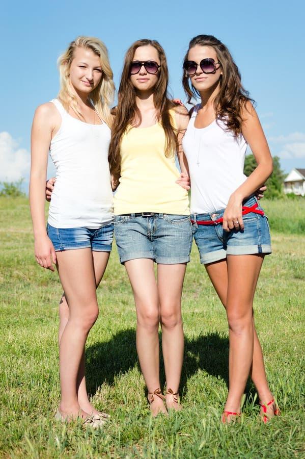 Trzy dziewczyna przyjaciela w cajgów skrótach nad niebieskim niebem obrazy royalty free