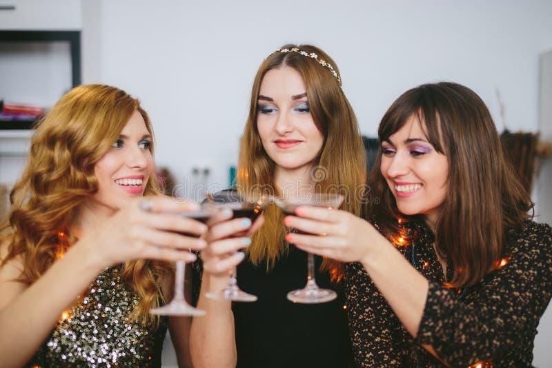 Trzy dziewczyny świętuje bożych narodzeń lub nowego roku ` s w domu wigilia obrazy stock