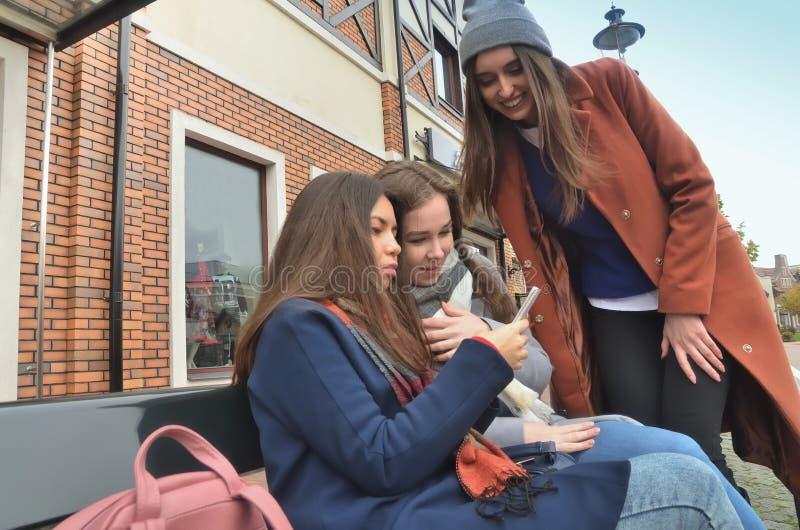 Trzy dziewczyny siedzą na ławce, ono uśmiecha się zdjęcie royalty free