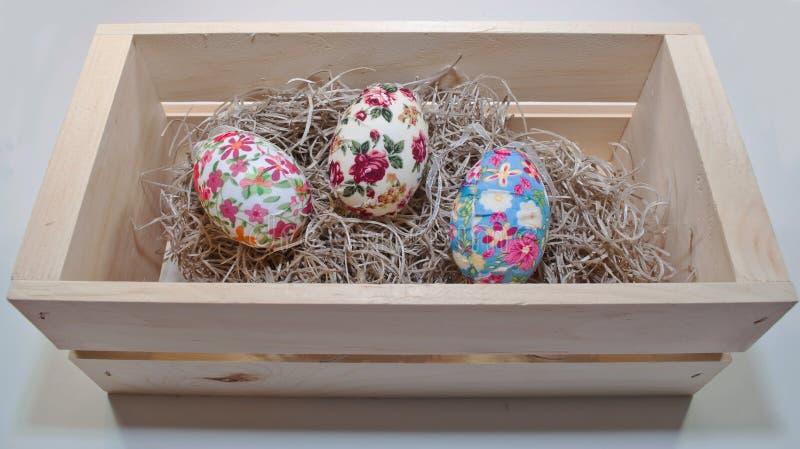 Trzy Easter jajka w drewnianym pudełku wypełniali z słomą obrazy stock