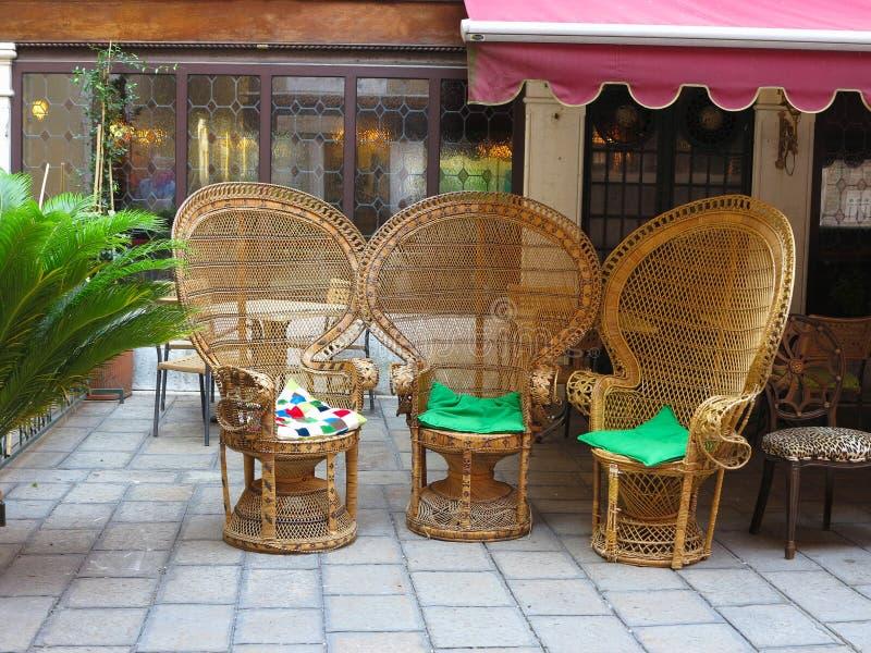 Trzy eleganckiego brown łozinowego krzesła w podwórka patiu zdjęcie royalty free
