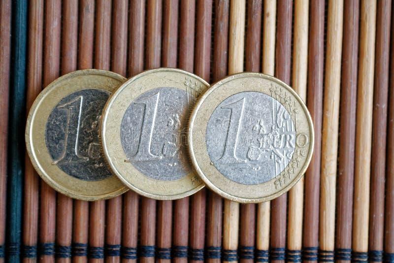 Trzy euro monety kłamają na drewnianym bambusa stołu wyznaniu z rzędu są jeden euro obrazy royalty free
